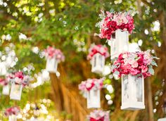 hang lanterns in the trees above each reception table with flower bouquets at the tops to add height and dimension to your wedding