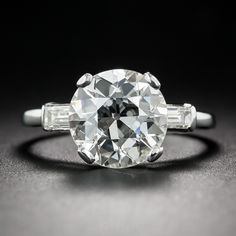 A gorgeous early-20th century European-cut diamond, weighing 3.01 carats, sparkles front and center in this consummate mid-century engagement ring. The scintillating center stone, classically presented in platinum between a pair of straight baguette diamonds, boasts exceptional proportions resulting in blinding fire and brilliance. Accompanied by a GIA Diamond Grading Report indicating J color and VS2 clarity. Timeless, traditional and seriously stunning. Currently ring size 5 3/4.