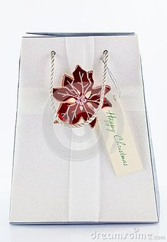 A white gift bag with a silk ribbon and a flower decoration.