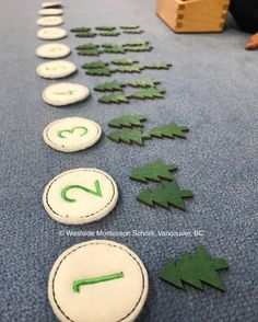 Adding seasonal counting to our Math shelf. The child lays out the numerals and builds the quantities with laser-cut wooden, painted trees from the Dollar Bins at Target. Great Montessori inspired early math activity during the holidays.