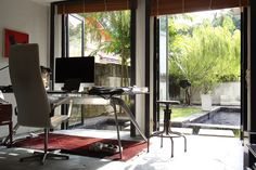 A cosy corner office opens up to a serene swimming pool and willow tree. (Photos…