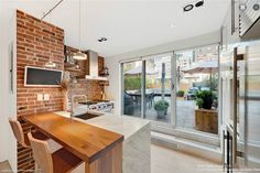 Kitchen, white cabinets, marble countertop, stainless steel, brick wall,hardwood floor, loft like, NYC, rooftop  Is This New York City's Best Six-Figure Penthouse? - On the Market - Curbed NY