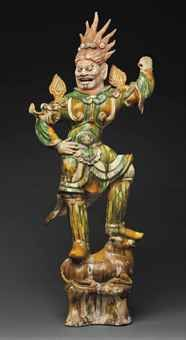 A WELL-MODELED SANCAI-GLAZED POTTERY FIGURE OF A LOKAPALA TANG DYNASTY (AD 618-907) The guardian is shown standing on top of a recumbent ox, his right hand placed on his hip and his left hand raised to hold a weapon. His unglazed face is painted red to accent the fierce expression and topped with radiating flame-like hair. He is dressed in elaborate armor surmounted by flames, all glazed in amber, green and cream. Loan Exhibition of the Arts of the T'ang Dynasty 36½ in. (92.7 cm.) high