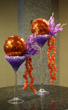 """""""Two Moons"""" Rich orange gazing balls sit atop the purple martinis. Gorgeous blue vanda orchids shoot out from the glass as the Japanese lanterns meander down the side."""