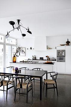 Køkkenet er udført af Simonsen & Czechura. På gulvet er valgt ølandsfliser, der giver et rustikt udtryk. Bordet er fra Tine K Home, og stolene er Wegners Y-stole i sort. Lampen over spisebordet er fra Serge Mouille.