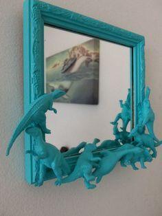Coller sur un cadre/miroir des dinosaures. Peindre avec de la peinture en bombe bleue.