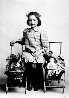 Little girl with her teddy bears and dolls in baby buggies, antique Edwardian photos, 1909.