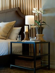 A glass and iron side table cozies up to the bed. Handmade acacia-wood pillars stagger the height of decorative accessories, including a phalaenopsis orchid in a glazed earthenware pot.