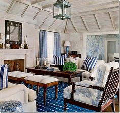 Phoebe Howard in Bermuda. Unbelievable bleached pine planking on this pitched sitting room ceiling. Stone walls are not only textural and a great color, but they keep the room cool. Lots of dark natural wood in the coffee table, chest on the far back corner, and set of spool chairs (so hot right now). Love the pair of footstools acting as a second coffee table in front of the foregrounded couch, and the green lantern. Beautiful layering of different blue and white fabrics as well.