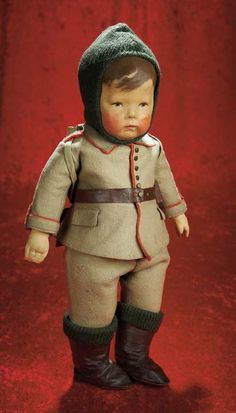 "Early Model German Cloth Character by Kathe Kruse in Original Costume  17"" (43 cm.) All-cloth doll with pressed and painted facial features,dark brown painted hair with forelock curl,small blue painted eyes with black upper eyeliner and brown eye shadow,accented nostrils of tiny nose,closed mouth with pouting lips,jointed shoulders and disc-jointed hips,separately-sewn thumb. Condition: very good,dent in left cheek. Marks: Kathe Kruse 1189 (feet)."