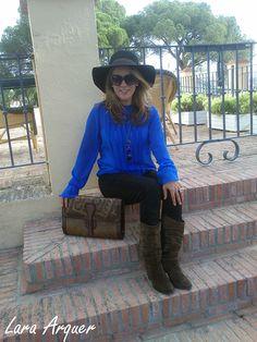 Cris con blusa azul klein, botas cowboy y sombrero. Estilismo chica trabajadora