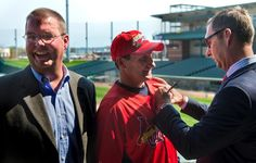 Peoria Chiefs president Rocky Vonachen laughs after officially signing a new player development contract with St. Louis Cardinals General Manager John Mozeliak, far right, during a public event at O'Brien Field Tuesday. Super fan Michael McNelis of Peoria Heights hops in to get an autograph. The Peoria Chiefs will open their 2013 regular season on April 4 against Wisconsin.