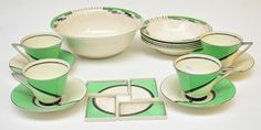 A Royal Doulton De Luxe Art Deco style part tea set decorated in chrome black and cream with a stylised sunrise comprising four cups, saucers and rectangular dishes, together with a similarly decorated part dessert service by Alfred Meakin in the Verdi pattern, printed marks #ukauctioneers #artdeco