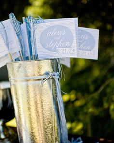 """Bride Alexis wrapped her ceremony programs around thin dowels; printed on the back of each were instructions for guests to cheer loudly and wave the program flags with """"great gusto"""" at the conclusion of the ceremony."""