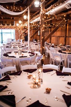 Elegant + rustic reception decor idea - white round banquet tables with plum-colored napkins and string lights {Kate McStay Photography}