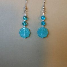Use the coupon code WEAREOPEN to save 10% on orders overs over $15 as a GRAND OPENING SPECIAL...Stainless steel hook earrings with clear blue-green acrylic beads that have a white splatter effect, glass white pearl seed beads and a cool green color acrylic flower shaped bead.