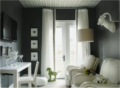 Dark grey TV room with large glass door with long sheer curtains, wallpapered ceiling, white leather armchairs with nail head trim, a white ...