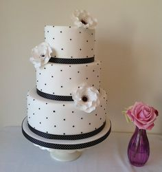 Black and white wedding cake. red roses instead and plain black ribbon instead of polka dotted.