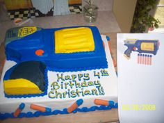"""Nerf Gun - For my boss's son.  I used a pic from Google to base it on.  Carved from a 9X13 using the scraps to make the barrell and other 3D effects.  The """"bullets"""" around the sides are rolled wafer cookies dipped in orange colored chocolate then blue buttercream with a blue m&m for the tip."""