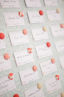 escort cards pinned to a board with cute flower tacks (various shades of pink and peach) pink and