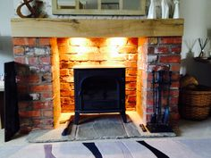 Stovax Stockton 8 multi-fuel stove, fireplace built from pre war common bricks with oak beam, Indian stone for the hearth, downlights in closuer plate.