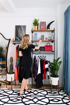 My home office! // industrial pipe wall-mounted clothing rack garment display units, white modern planters with wooden leg base, blue silk curtains draperies, black and white area rug, framed zebra art, large leaner oversized floor mirror, eclectic interior design, home decor