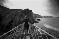 Carrick-a-Rede. Woman blinded by her own hair crossing the rope bridge over chasm to Carrick Island. Ian Berry, Columbia College Chicago, Rope Bridge, Pro Bono, Photography Workshops, Northern Ireland, Afghanistan, Uganda, Geometry