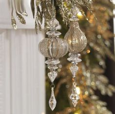 "7.5"" Drop Ornaments. These delicate ornaments are strung together by wire.  The blown glass bulb is connected to resin dangling crystals. then some parts are encrusted in silver sparkles.      made of resin and glass    Clear/Gold    7.5"" long"