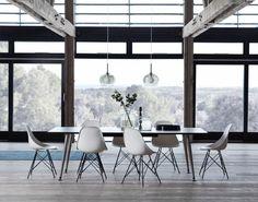 salle à manger moderne aménagée avec une grande table rectangulaire en noir et alu et entourée de chaises design en blanc et noir