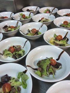 Preparación de los platos de ensalada con ceviche de atún cocinado con limón y cebolla.