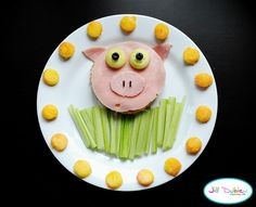 from meet the dubiens      Cut a circle out of a piece of bread, layer on a piece of cheese, and a piece of ham lunch meat. Using another piece of ham, cut out a nose and ears. I used cucumbers and blueberries for the eyes, and 2 chocolate sprinkles for the nose. The 'grass' is celery sticks, and I put peaches around the outside of the plate.