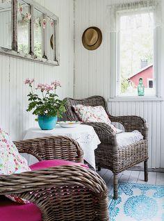 Verannan seinät maalattiin valkoisiksi. Ikean korituolit saivat pehmusteeksi tyynyt Marikan suosikki-kuosista, kukallisesta paisleystä. Matto on Tiimarista.