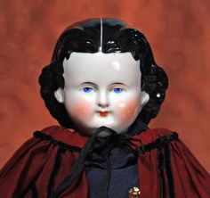 "GERMAN PORCELAIN LADY WITH ""ADELINA PATTI"" HAIRSTYLE BY ALT, BECK & GOTTSCHALCK. 18 ½"". Porcelain shoulderhead, painted and sculpted black hair in the ""Adelina Patti"" style with partially-modelled ears, painted features, shaded blue eyes, red and black lid lines, tapered brows, blushed cheeks, closed mouth, original cloth body with porcelain lower limbs, painted brown boots with black trim, gilt buttons blue tassels, wears antique maroon wool cape over fitted navy blue dress. Estimate…"