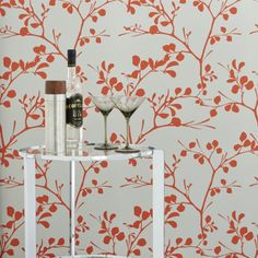 Leafy branches flourish in a bold botanical design by Chicago-based artist Noël Ashby. Capturing the liveliness of a tree, graphic silhouettes pop in red/orange on light grey.