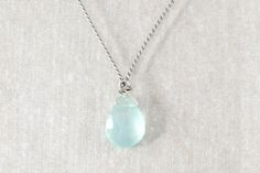 Dainty handmade pastel blue teardrop gemstone necklace.Materials:Chalcedony semi-precious gemstone, sterling silver, grey pearl cotton thread.  For sale on http://hellopretty.co.za