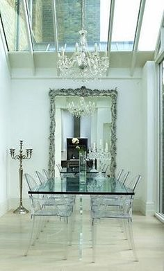 Beautiful mirror, ghost chairs, chandelier, candelabra, lots of glass and natural light. Simple, modern, classic, beautiful.