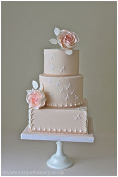 Butterfly Rose Wedding Cake. Romantic barely blush iced wedding cake with square base and large sugar roses, pearls detail and butterflies. Featured in Tatler weddings.