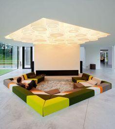 O formato pentagonal da luminária no teto foi replicada no piso, com um sofá rebaixado super colorido.