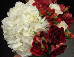 A bridal bouquet consisting of white hydrangea, red roses and red hypericum berries.