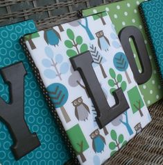 Fabric on canvas with wooden letters.  Much better than just letters on a wall.