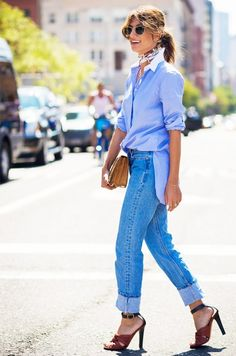 A crisp oxford shirt is worn with a silk scarf, cuffed jeans, ankle-strap sandals, and a clutch