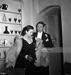 Sir Laurence Olivier places a fur coat on the shoulders of his wife Vivien Leigh as they leave their Chelsea cottage for the Leicester Square theatre to attend the World premiere of the film 'Anna Karenina', 1948