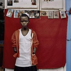 Liberia, Monrovia, May 2004. Ex-combatant poses for an outside studio portrait on Broad Street. The boy was recruited to fight for Charles Taylor's forces. He was caught during the fighting by LURD rebel forces, who cut his hands off and sent him back to Monrovia. Tim Hetherington.