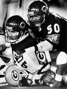 Gary Fencik #45 (FS) and Mike Singletary #50 (LB), part of the ferocious 1985 Chicago Bears defense, plows over Eddie Lee Ivory #40 (RB) of the Green Bay Packers in a 23-7 Bears win.