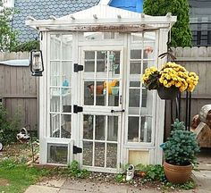 greenhouse built from vintage windows tied together with wood, a small pitched roof, and a handsome arbor, all painted white, sits in a yard area against a tall wood fence with other homes in the background and planting all around