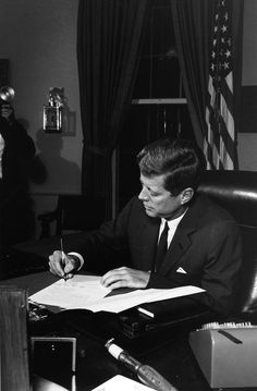 President Kennedy signing the Cuban naval quarantine proclamation at the White House, 23 October 1962.