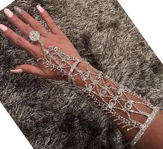 Jennie Hand Chain Slave Ring Bracelet. Gorgeous Sparkling Hand Wedding Jewelry. Slave Hand Harness Bracelet Ring. Embellished with hundreds of sparkling rhinestones. Perfect for a Bollywood Wedding. Add something Unique and Elegant for the Arms of the Bride Panja   Adjustable Size.Iridescent AB Color Rhinestones.   MADE TO ORDER: Please Allow Two Weeks Production Time.