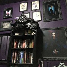gorgeous gothic style bookshelf against a purple (eggplant) wall and miss matched black baroque picture frames