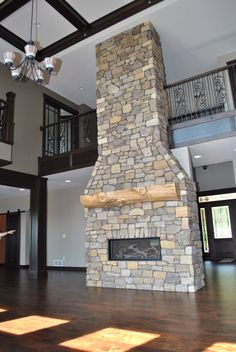 A gorgeous stone fireplace made even more gorgeous with the addition of a log mantle. This design is by C&M Home Builders and Real Estate in Eau Claire, Wis.