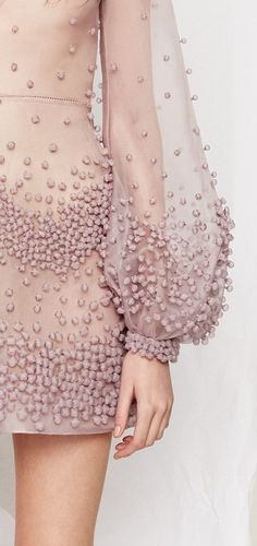 Dramatic beading on a sheer lavender pink gown.